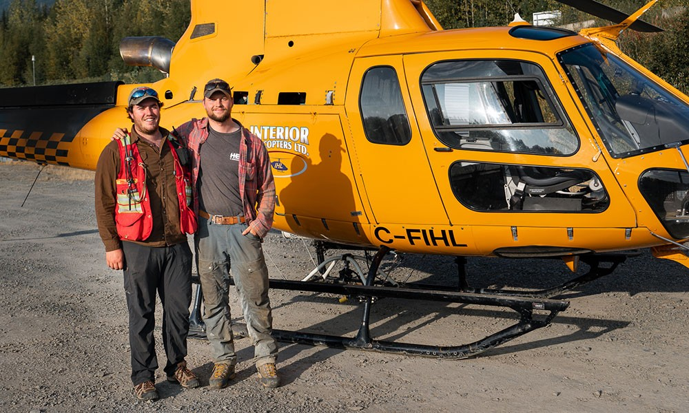 UBCO alumni Cole Evans and Dylan Hunko in front of the helicopter that will take them into the remote Canadian wilderness.