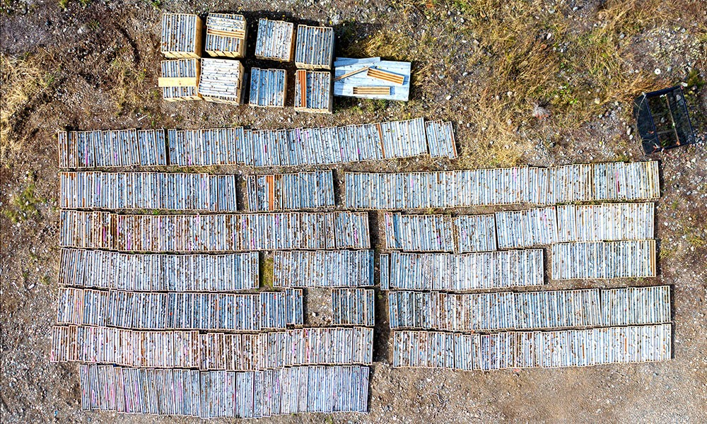"""Drill core mineralized with gold and copper are laid out on the ground for a """"quick log"""" prior to being processed."""