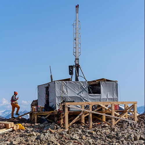 Cole Evans communicates by VHF radio as he inspects a diamond drill on a mountain top in BC's famed Golden Triangle.