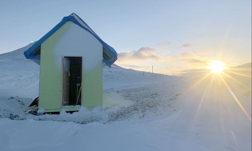 The sun sets on a makeshift survival shelter at 7,000 feet near the Andrei Ice field in northwestern British Columbia.